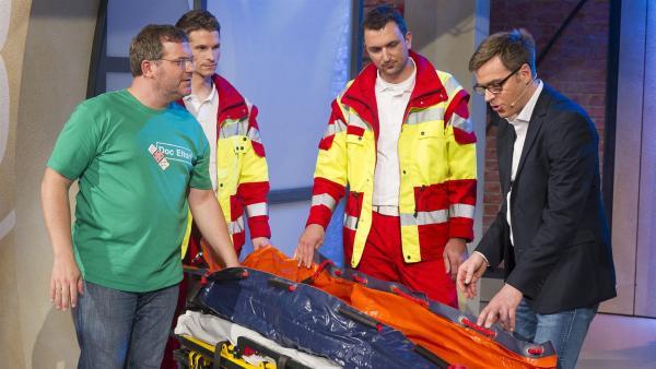 Dr.med. Alexander Hauber und zwei Sanitäter erklären Elton, wie die Vakuummatratze funktioniert. | Rechte: ZDF/Ralf Wilschewski