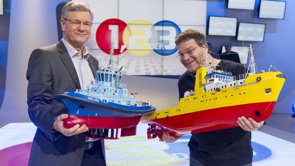 Dr. Dirk Jürgens und Elton mit zwei Modellen von Hafenschleppern.   Rechte: ZDF/Ralf Wilschewski