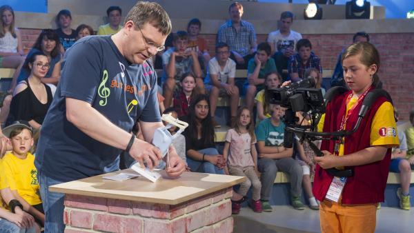 Elton demonstriert dem Kamerakind Mariella, wo die Stimmbänder sitzen.   Rechte: ZDF und Ralf Wilschewski