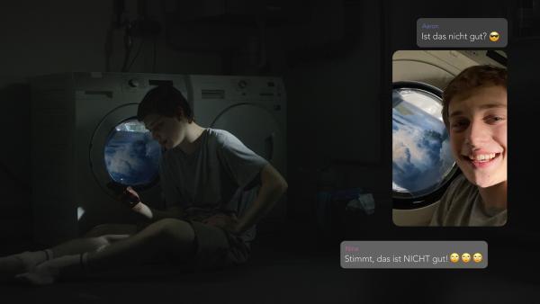Aarons (Philip Müller) erster Versuch eines Fake-Fotos mit Waschmaschinenfenster ist nicht gut. | Rechte: KiKA/2021 eitelsonnenschein