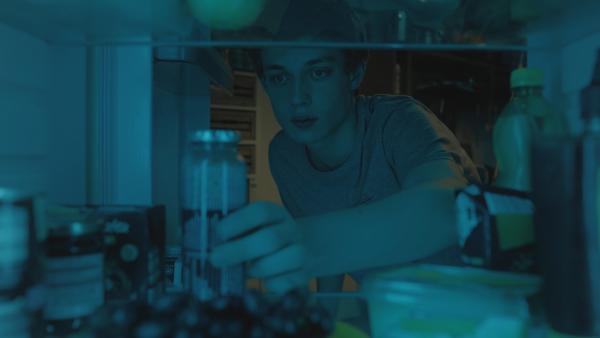 Aaron (Philip Müller) sucht im Kühlschrank nach dem Tomatensaft. | Rechte: KiKA/2021 eitelsonnenschein