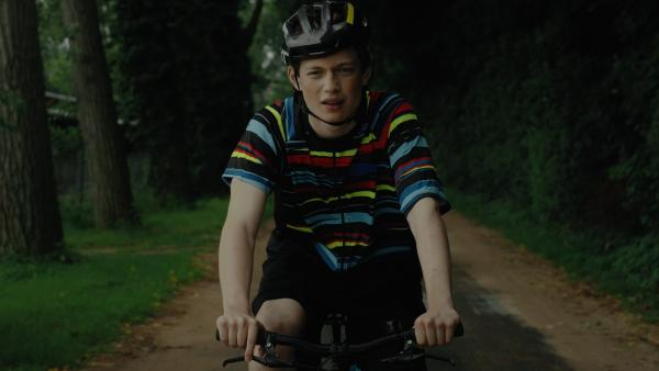 Aaron (Philip Müller) fährt auf dem Fahrrad.   Rechte: KiKA/2021 eitelsonnenschein