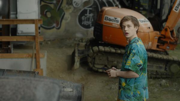 Aaron (Philip Müller) sucht sich einen Sandhaufen um ein Strand- & Sandfoto zu faken. | Rechte: KiKA/2021 eitelsonnenschein