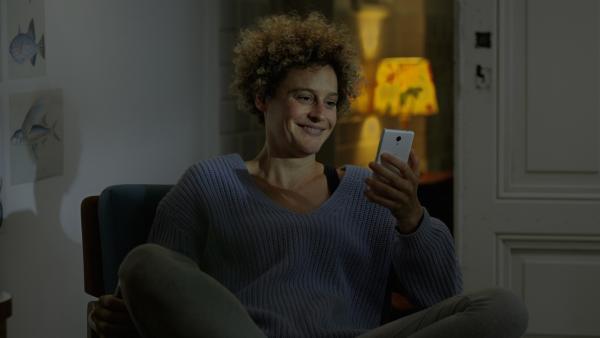 Jenny (Karen Dahmen) telefoniert mit Aarons Mutter Nadine und ist ganz zufrieden nach einem guten Gespräch mit Aaron. | Rechte: KiKA/2021 eitelsonnenschein