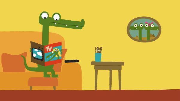 Das Krokodil studiert das Programm.   Rechte: KiKA/SWR/Film Bilder/Julia Ocker