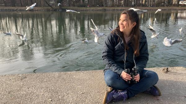 Wie lacht die Lachmöwe? / Anna sitzt an der Isar und beobachtet Lachmöwen mit dem Fernglas. | Bild: BR/TEXT + BILD Medienproduktion GmbH & Co. KG | Rechte: BR/TEXT + BILD Medienproduktion GmbH & Co. KG