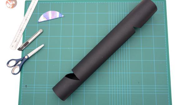 Schneide in die Papprolle mit deinem Bastelmesser jeweils am oberen und unteren Ende vorsichtig zwei keilförmige Löcher im 45° Winkel. Beachte, dass die beiden Ausschnitte jeweils auf der gegenüberliegenden  Seite liegen müssen. Das bedeutet,  wenn du die Röhre vor dir aufstellst, befindet sich eine Öffnung oben und auf der Rückseite eine Öffnung unten.  | Rechte: KiKA