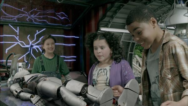 Stolz zeigt Anne (Addison Holley, li.), Shania (Adrianna Di Liello, Mi.) und Nick (Jadiel Dowlin, re,) ihren Androiden PAL (Millie Davis). | Rechte: KiKA/Sinking Ship Entertainment