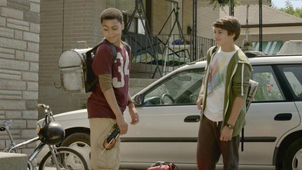 Nick (Jadiel Dowlin, li.) ibekommt einen Rucksack von seinem Freund Zack (Jonny Gray, re.) geschenkt.   Rechte: KiKA/Sinking Ship Entertainment