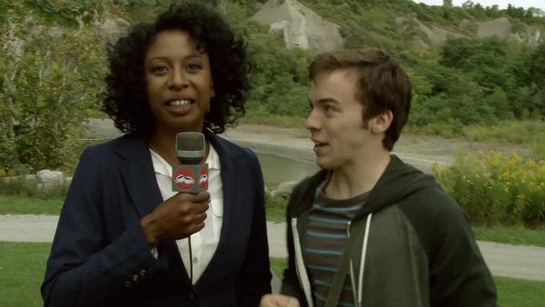 Maggie (Raven Dauda) interviewt einen Meteoritenjäger. | Rechte: KiKA/Sinking Ship Entertainment