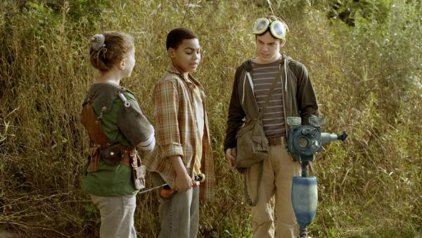 Nick (Jadiel Dowlin) und Anne (Addison Holley) versuchen Eyes vor einem Meteoritenjäger zu verstecken. | Rechte: KiKA/Sinking Ship Entertainment