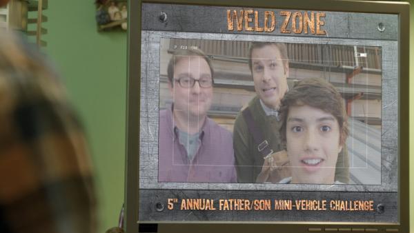 Zack (Jonny Gray) und seine Dads geben die Herausforderung für das Vater-Sohn-Modellfahrzeugrennen bekannt. | Rechte: KiKA/Sinking Ship Entertainment