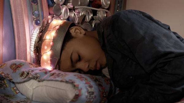 Nick (Jadiel Dowlin) schläft mit Annes Hirnstrom-Messgerät. | Rechte: KiKA/Sinking Ship Entertainment