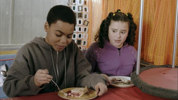 Anhand eines gefüllten Kuchens erklärt Anne Nick (Jadiel Dowlin) und Shania (Adrianna Di Liello) die Erdkruste. | Rechte: KiKA/Sinking Ship Entertainment