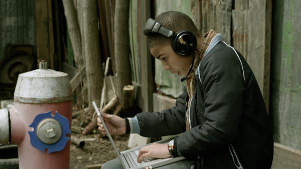Nick (Jadiel Dowlin), der nicht auf den Schrottplatz darf, unterstützt Shania per Webcam und Computer. | Rechte: KiKA/Sinking Ship Entertainment