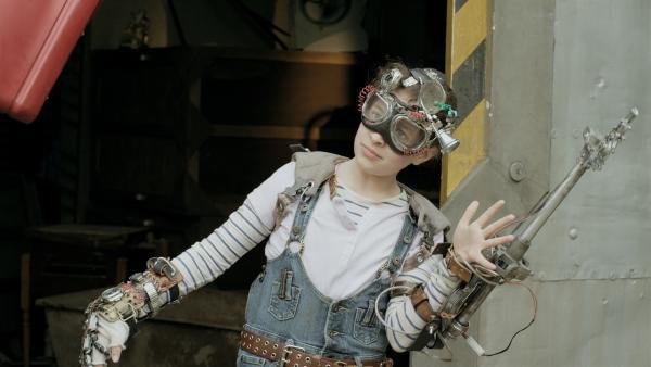 """Anne (Addison Holley), als Android """"verkleidet"""", begrüßt Maggie auf dem Schrottplatz.   Rechte: KiKA/Sinking Ship Entertainment"""