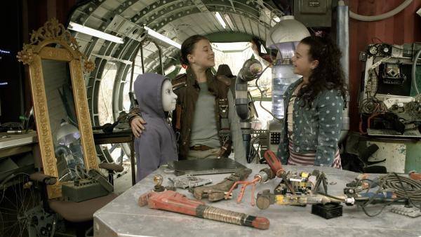 Anne (Addison Holley) führt Shania (Adrianna Di Liello) PAL (Millie Davis) in seinem neuen Kostüm vor.   Rechte: KiKA/Sinking Ship Entertainment