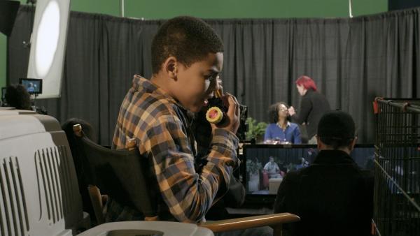 Nick (Jadiel Dowlin) ist bei seiner Mutter im Fernsehstudio und hält Kontakt zum Schrottplatz-Team. | Rechte: KiKA/Sinking Ship Entertainment