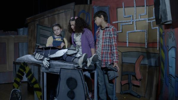 Shania (Adrianna Di Liello) probt mit ihren Mitschülern das Theaterstück, das die Geschichte ihrer Freundschaft mit Anne, Nick und PAL erzählt. | Rechte: KiKA/Sinking Ship Entertainment