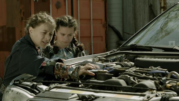 Anne (Addison Holley) und Shania (Adrianna Di Liello) begutachten den Motor von Maggies kaputtem Auto.   Rechte: KiKA/Sinking Ship Entertainment