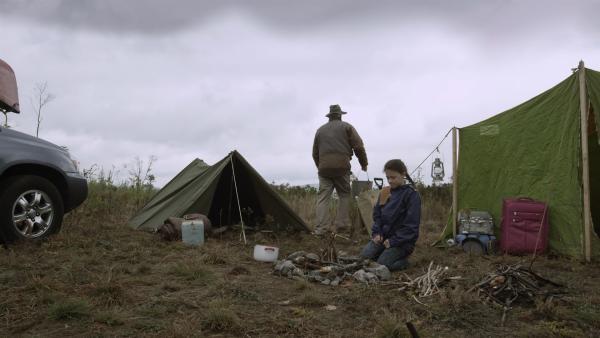 Während Mr. Cooper das Zelt aufbaut, bereitet Anne (Addison Holley) ein Lagerfeuer vor. | Rechte: KiKA/Sinking Ship Entertainment
