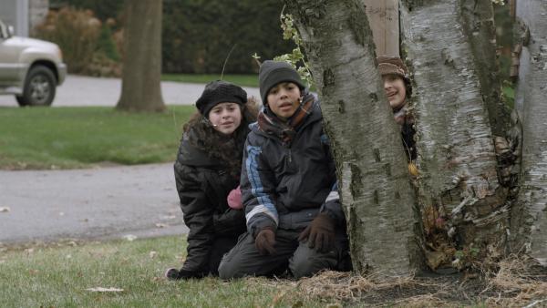 Shania (Adrianna Di Liello), Nick (Jadiel Dowlin) und Anne (Addison Holley) warten vor Adas Haus auf eine günstige Gelegenheit, um in Adas Haus vorzudringen.   | Rechte: KiKA/Sinking Ship Entertainment