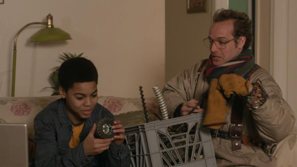 Wilbert (James Gangl) bringt Nick (Jadiel Dowlin) ein paar Dinge für die Konstruktion eines Modellfahrzeugs, die er auf dem Schrottplatz gefunden hat. | Rechte: KiKA/Sinking Ship Entertainment