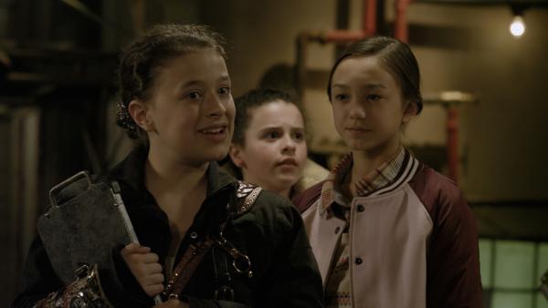 Anne (Addison Holley) erklärt Shania (Adrianna Di Liello) und Charlie (Devyn Nekoda), worauf sie achten müssen, wenn sie für Anne den Schrottplatz und die Androiden bewachen. | Rechte: KiKA/Sinking Ship Entertainment