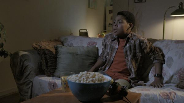 Nick (Jadiel Dowlin) hat noch immer Schrottplatzverbot und muss den Abend allein vor dem Fernseher verbringen.  | Rechte: KiKA/Sinking Ship Entertainment