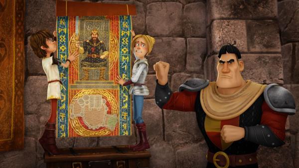 Arthur, Tristan und ihr Lehrer Ulfin hängen den Wandteppich auf, den König Uther bekommen hat.   Rechte: SWR/Blue Spirit Productions/TéléTOON+/Canal+