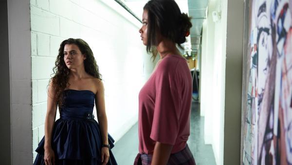 Nyela (Ella Balniska, li.) steht erwartungsvoll vor dem Kursraum. Sie hat ein Kleid für ihre Kommilitonin Leigh (Tafline Steen, re.) entworfen, das bewertet werden soll. | Rechte: ZDF/Depesche/Des Willie 20