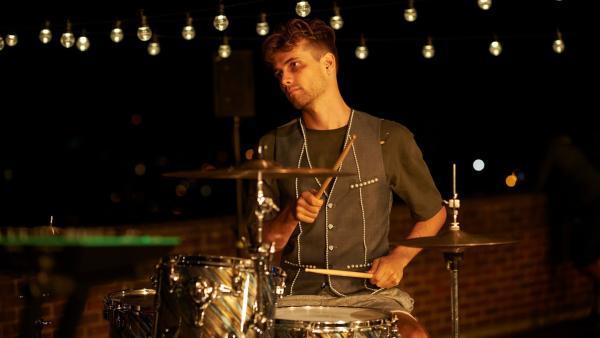 Sam (Oliver Dench), der am Athena-College Schmuckdesign studiert und auf den Nyela ein Auge geworfen hat, probt am Schlagzeug.   Rechte: ZDF/Depesche/Des Willie