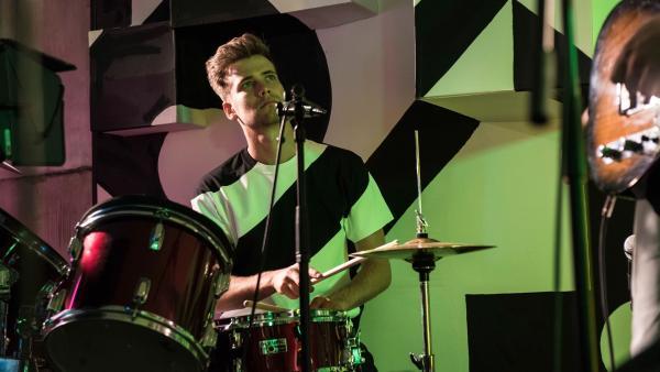 Sam (Oliver Dench) spielt mit seiner Band ein Konzert am Athena-College. Doch er kann seine Gedanken nicht von Nyela lassen, die heute ein Date mit einem anderen hatte. | Rechte: ZDF/Depesche/Holly Wren
