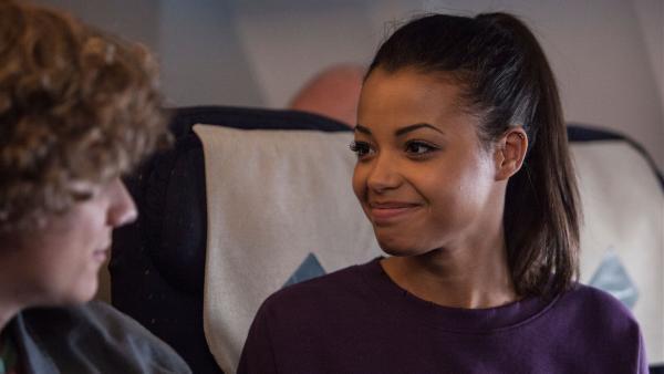 Nyela (Ella Balinska re.) will nach ihrem Rausschmiss aus der Athena nach Deutschland zu ihren Eltern fliegen. Zufällig trifft sie im Flugzeug auf Lenny (Basil Eidenbenz, li.), der dasselbe vorhat. | Rechte: ZDF/Depesche/Luke Varley