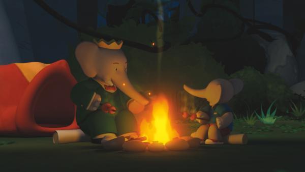 Babar und Badou essen Beeren am Stock beim Lagerfeuer. | Rechte: KiKA/Nelvana Limited