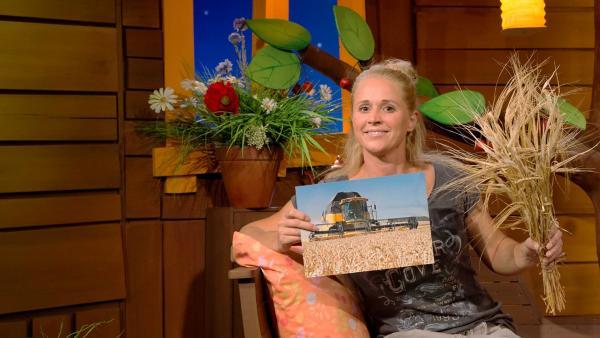 Singa zeigt ein Bild von einem Mähdrescher und Getreide. | Rechte: KiKA