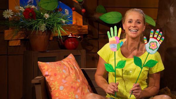 Singa zeigt ihre gebastelten Blumenhände. | Rechte: KiKA