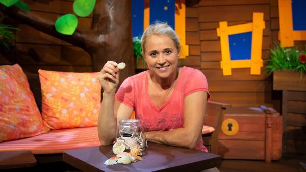 Singa dekoriert ein Glas mit Muscheln. | Rechte: KiKA/Dorit Jackermeier