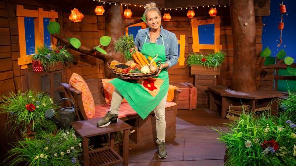 Singa hat viele Früchte mitgebracht: Brombeeren, Kartoffeln, Äpfel und einen dicken Kürbis. In ihrem Garten ist nämlich  jetzt Erntezeit – und was Ernte eigentlich ist, das erklärt sie gleich auch noch. | Rechte: KiKA/Nadja Usbeck