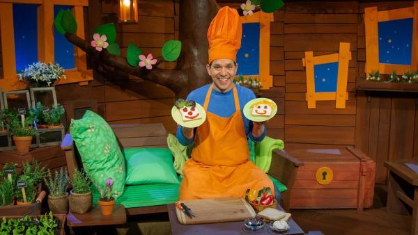 Juri legt Gemüsegesichter auf sein Brot. | Rechte: KiKA/Hannah Michalowicz