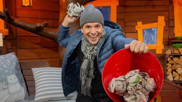 Juri macht eine Schneeballschlacht mit Zeitungspapier. | Rechte: KiKA/Josefine Liesfeld