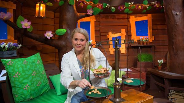 Singa wiegt Kekse mit einer Balkenwaage. | Rechte: KiKA/Josefine Liesfeld