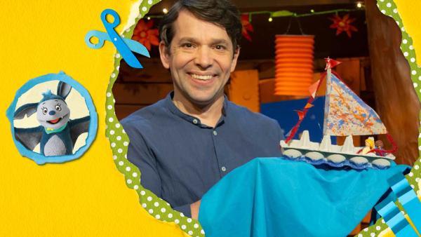 Juri bastelt aus einem Eierkarton, Pappe und bunten Bändern ein Segelschiff. Mal es mit Wasserfarben bunt an! | Rechte: KiKA
