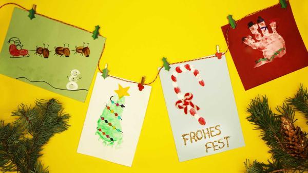 Verschiedene selbstgemachte Weihnachtskarten aus Handabdrücken und Fußabdrücken sind mit Klammern an einer Schnur befestigt. | Rechte: KiKA