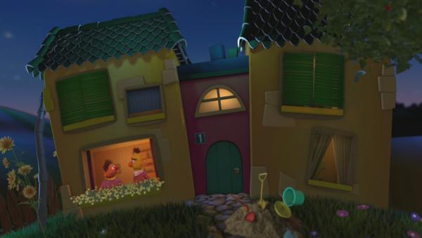Ernie und Bert schauen aus dem Gute-Nacht-Haus vor dem Sonnenblumen blühen. | Rechte: KiKA