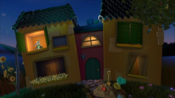 Fidi schaut aus dem Gute-Nacht-Haus und erzählt von ihrem fiditionellen Tag. Vor dem Gute-Nacht-Haus ist eine Sandburg mit Sandspielzeug, wie ein Eimer, Sieb und Schaufel. | Rechte: KiKA