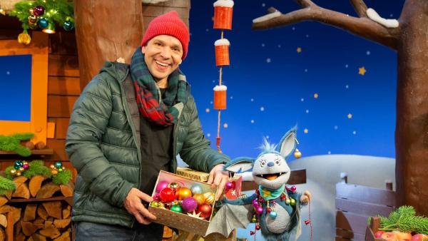 Juri zeigt Fidi den Weihnachtsschmuck für den Weihnachtsbaum und singen das Adventslied.  | Rechte: KiKA/Nadja Usbeck