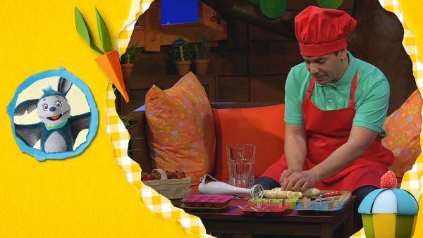 Juri schneidet mit einem Messer eine Banane klein. Er rtägt eine tote Kochschürze und eine rote Kochmütze. | Rechte: KiKA
