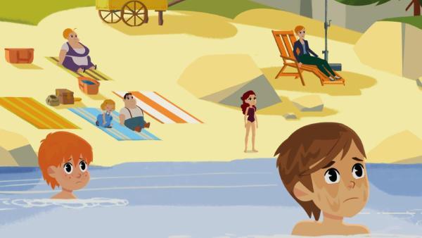 Die Dorfbewohner genießen ihre Zeit am Strand. Zwei Jungen im Wasser blicken erschrocken auf etwas Herannahendes. | Rechte: © 2017 Gaumont Animation, PVP Animation III Inc.- All rights reserved