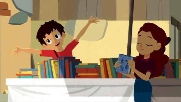 Sebastian steht hinter einem Tisch voller Bücher und wirft fröhlich die Arme nach oben. Adele steht davor und hält ein Buch in der Hand.   Rechte: © 2017 Gaumont Animation, PVP Animation III Inc.- All rights reserved